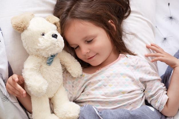 Adorable petite fille se coucher avec les yeux fermés, enfant portant un pyjama blanc allongé sur un lit blanc, dormir dans une chambre confortable