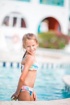 Adorable petite fille se détendre à la piscine extérieure