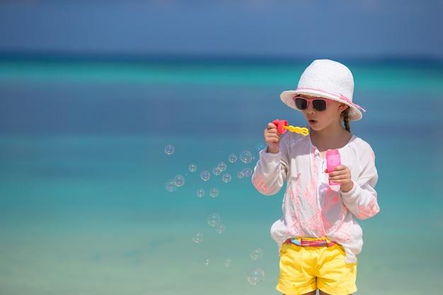 Adorable petite fille soufflant des bulles de savon sur la plage
