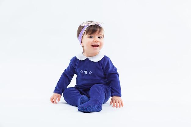 Adorable petite fille souriante mignonne avec un arc dans les cheveux assis posant sur blanc