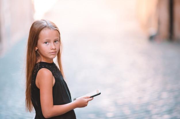 Adorable petite fille avec un téléphone portable dans une ville italienne pendant les vacances d'été