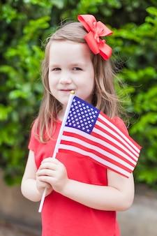 Adorable petite fille tenant un drapeau américain à l'extérieur sur une belle journée d'été