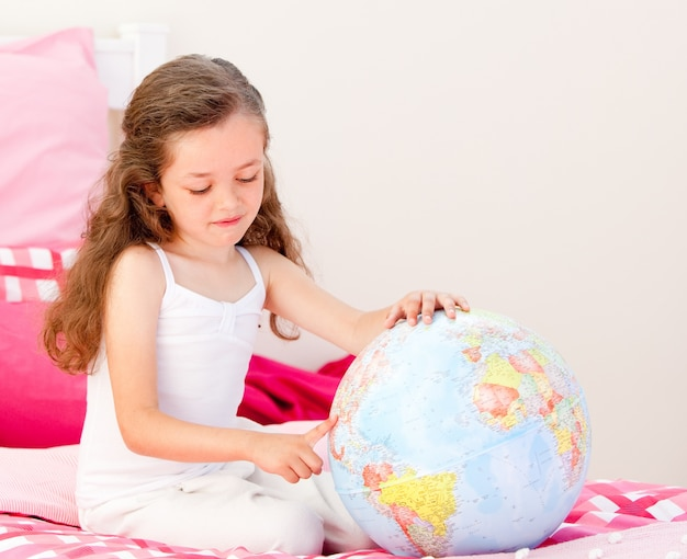 Adorable petite fille tenant un globe terrestre assis sur son lit