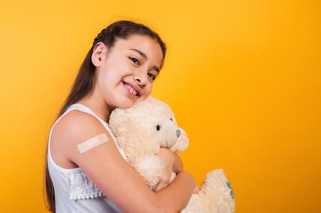 Adorable petite fille tenant un ours en peluche avec un pansement sur son bras.