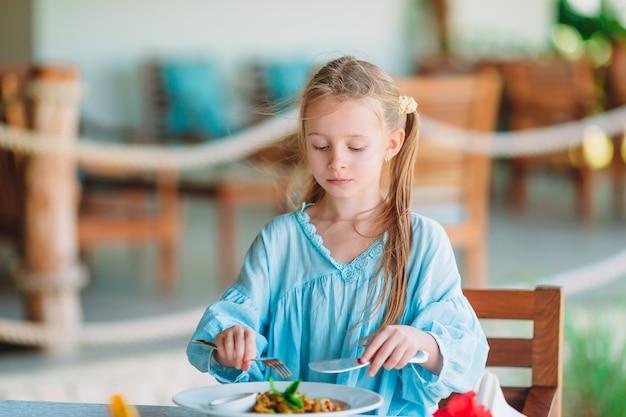 Adorable petite fille en train de dîner au café en plein air