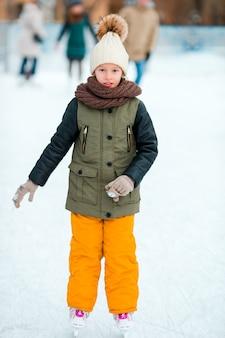 Adorable petite fille va patiner en hiver journée de neige à l'extérieur