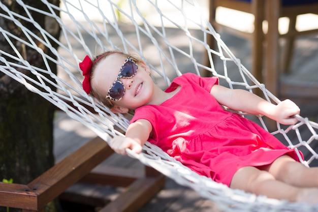 Adorable petite fille en vacances tropicales se détendre dans un hamac