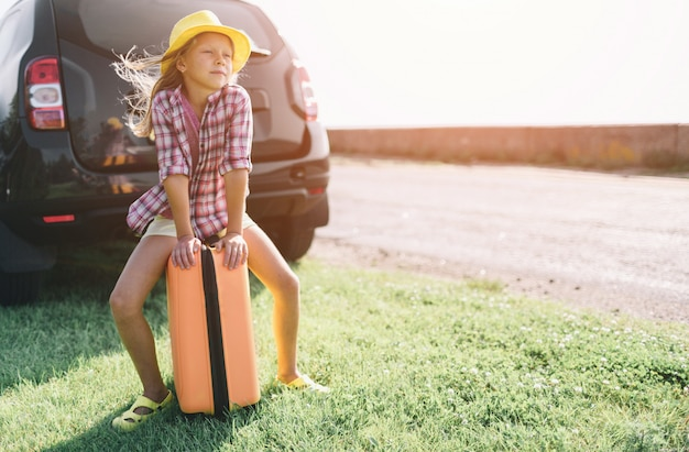 Adorable petite fille avec une valise partant en vacances en voiture avec leurs parents