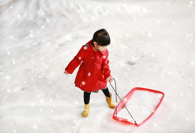 Adorable petite fille vêtue d'une veste rouge s'amuse dans la neige