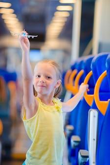 Adorable petite fille voyageant en train et s'amusant avec le modèle d'avion dans les mains