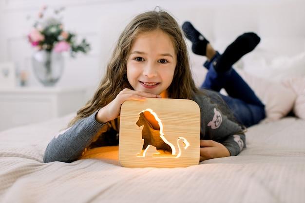 Adorable petite jolie fille allongée sur le lit dans une pièce lumineuse confortable et jouant avec une lampe de nuit en bois avec une image de lion découpée.