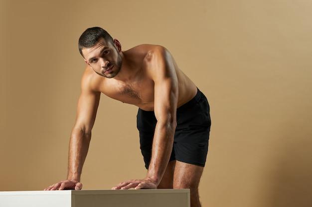 Adorable sportif barbu en short mettant sa main sur un bureau blanc dans la chambre à l'intérieur