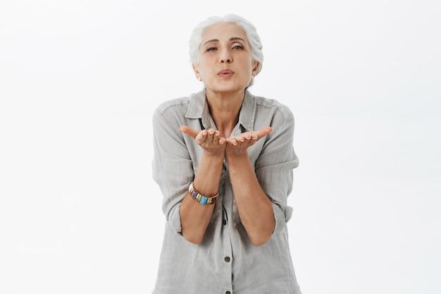Adorable vieille dame aux cheveux gris souffle de l'air baiser