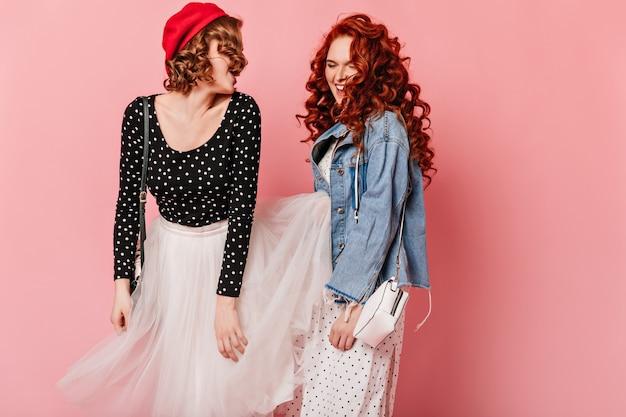 Adorables dames dansant sur fond rose. photo de studio d'amis joyeux s'amusant ensemble.