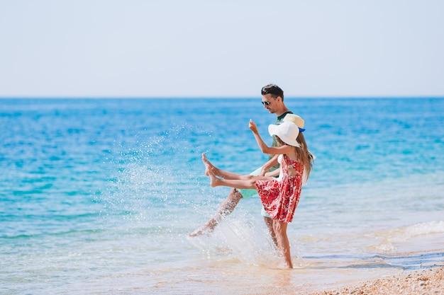 Adorables enfants et leur père à la plage pendant les vacances d'été