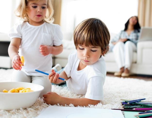 Adorables enfants mangeant des frites et dessinant