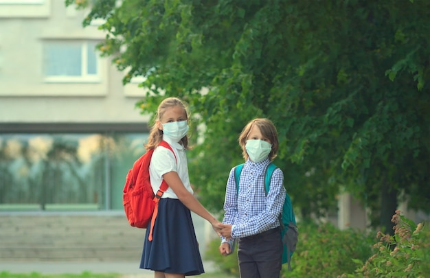 Adorables enfants portant des masques faciaux à l'école