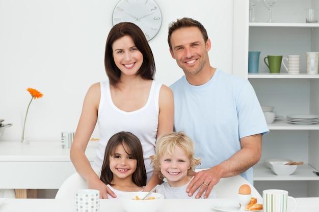 Adorables enfants posant avec leurs parents dans la cuisine