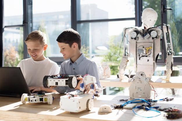 Adorables enfants pré-adolescents inspectant un atelier de véhicules robotiques