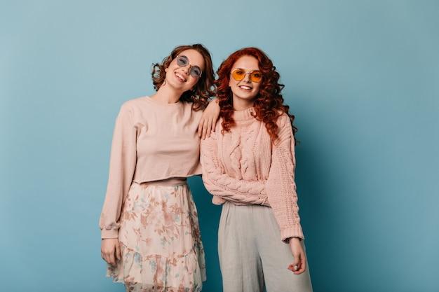 Adorables filles en lunettes de soleil regardant la caméra. vue de face d'amis souriants isolés sur fond bleu.
