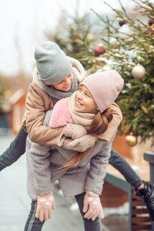 Adorables filles patinant sur la patinoire à l'extérieur en hiver journée de neige