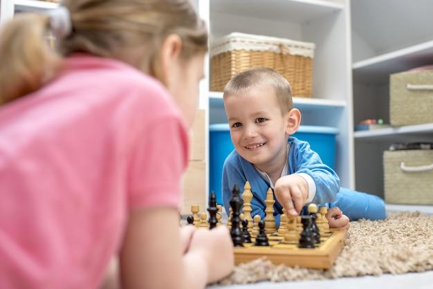 Adorables frères et sœurs allongés sur le sol et jouant aux échecs les uns avec les autres