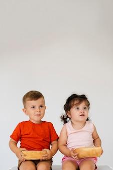 Adorables jeunes frères et sœurs tenant du pain