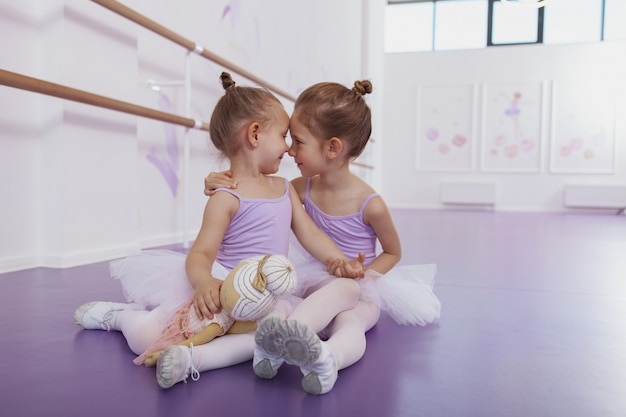Adorables petites ballerines se frottant le nez, s'amusant à l'école de ballet