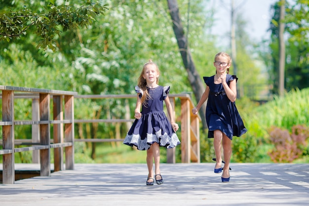 Adorables petites écolières à l'extérieur par une chaude journée de septembre. retour à l'école.