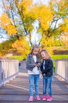 Adorables petites filles au chaud jour d'automne en plein air