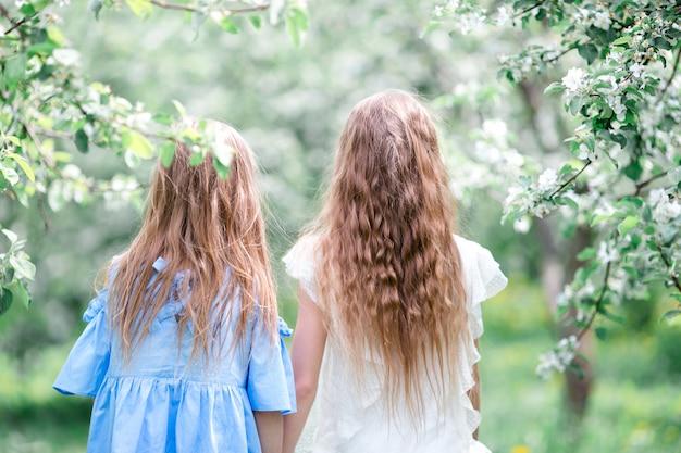Adorables petites filles dans le jardin fleuri du pommier le jour du printemps