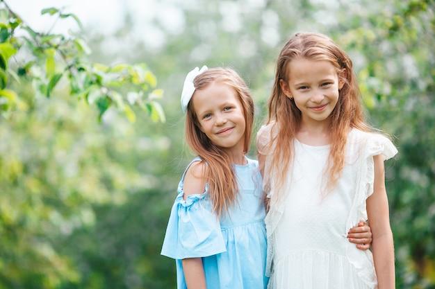Adorables petites filles dans le jardin de pommiers en fleurs le jour du printemps
