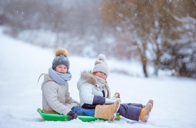 Adorables petites filles heureuse en traîneau en jour de neige d'hiver.