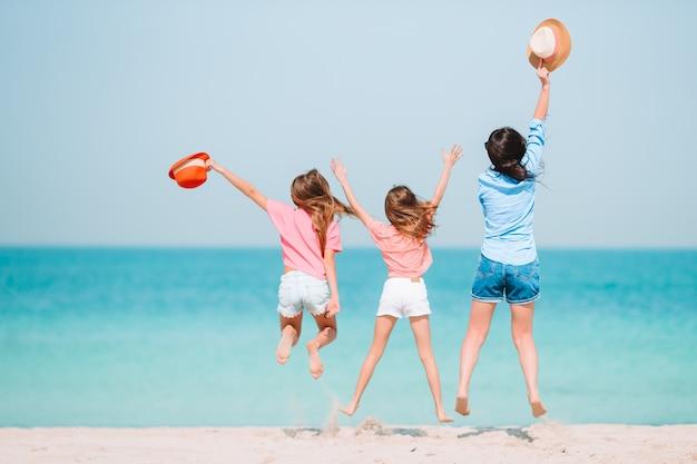 Adorables petites filles et jeune maman sur la plage blanche tropicale