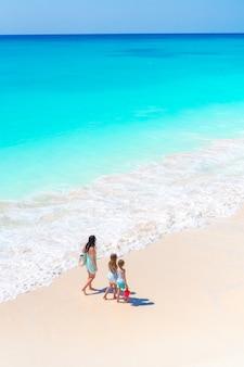 Adorables petites filles et jeune maman sur la plage blanche. vue sur la famille et l'océan d'en haut