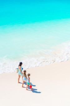 Adorables petites filles et jeune maman sur la plage blanche
