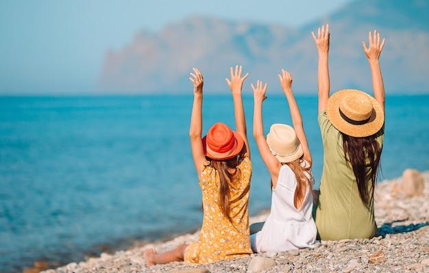 Adorables petites filles et jeune mère sur la plage blanche tropicale