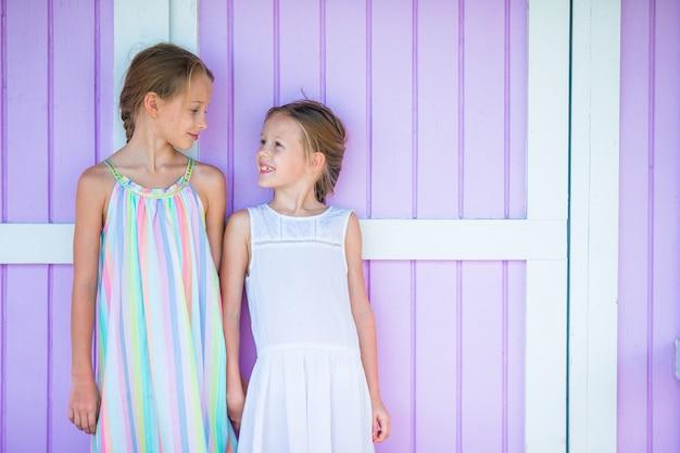 Adorables petites filles sur la maison traditionnelle des caraïbes colorée