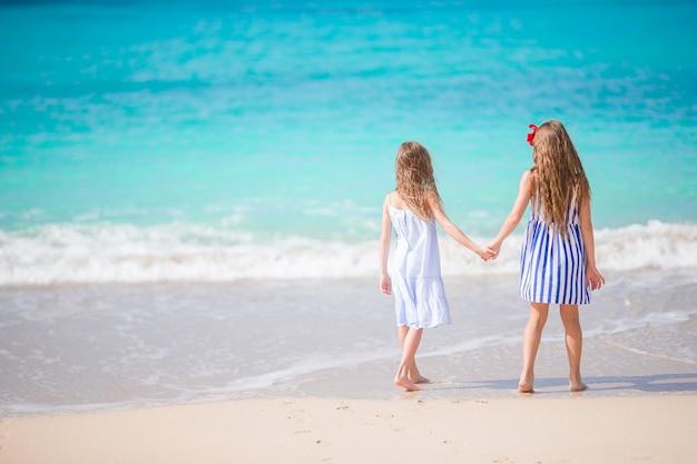 Adorables petites filles marchant sur la plage