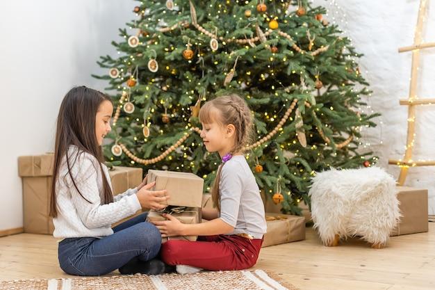 Adorables petites filles ouvrant un cadeau de noël magique par un arbre de noël dans un salon confortable en hiver