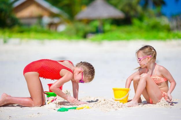 Adorables petites filles pendant les vacances d'été. enfants jouant avec des jouets de plage sur la plage blanche