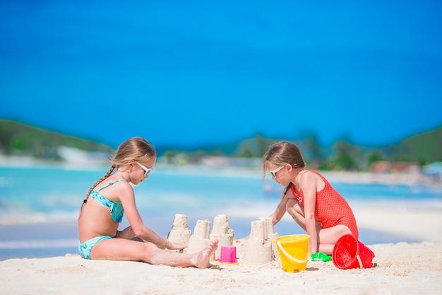 Adorables petites filles pendant les vacances d'été sur la plage