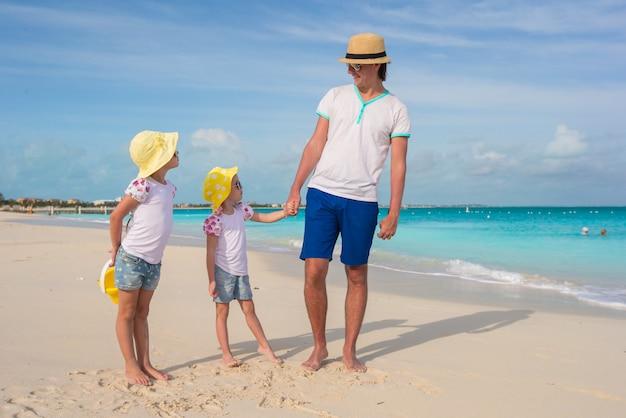 Adorables petites filles et père heureux sur la plage blanche tropicale