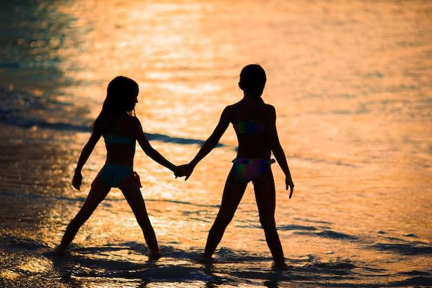 Adorables petites filles sur la plage avec un beau coucher de soleil coloré