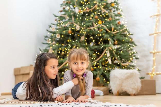 Adorables petites filles près d'un arbre de noël dans un salon confortable en hiver