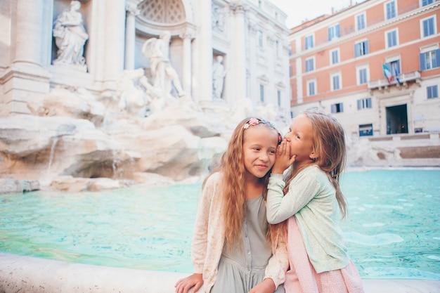 Adorables petites filles près de la fontaine de trevi à rome.