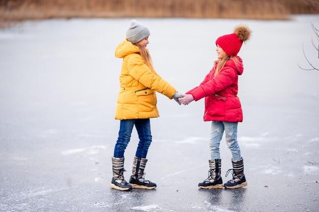Adorables petites filles qui patinent sur la patinoire