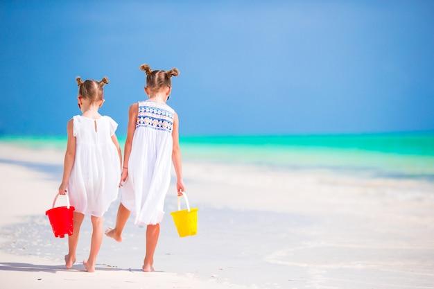 Adorables petites filles s'amusant pendant les vacances à la plage