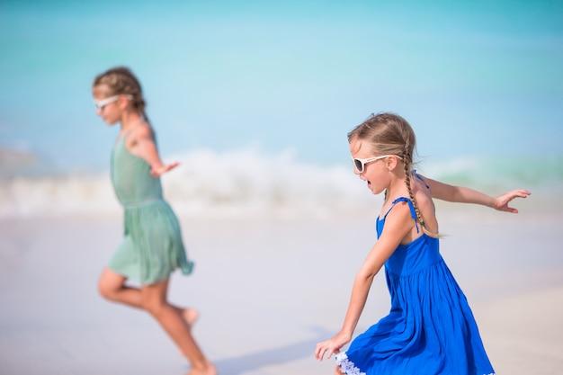 Adorables petites filles s'amusent beaucoup sur la plage.