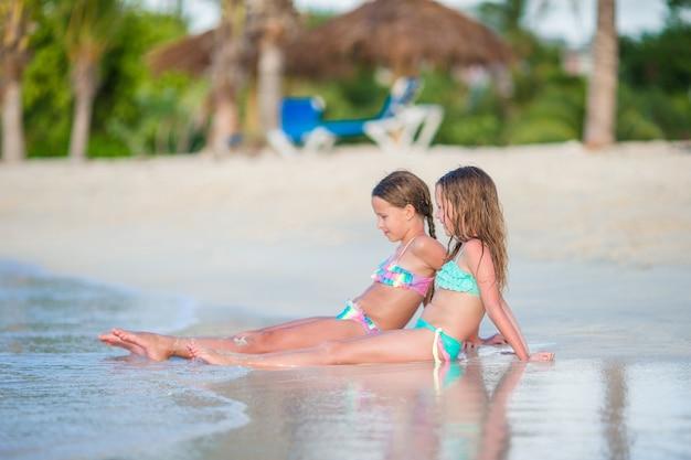 Adorables petites filles se détendre sur la plage